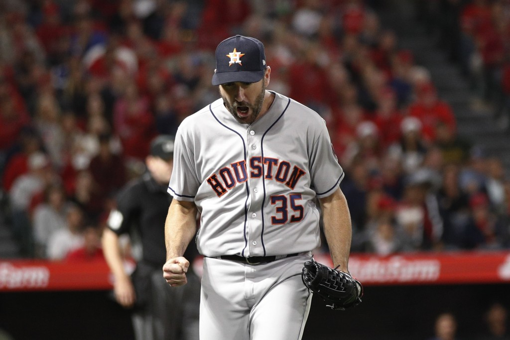 Houston Astros starting pitcher Justin Verlander clenches his fist after getting the last out in the eighth inning of the team's baseball game against...