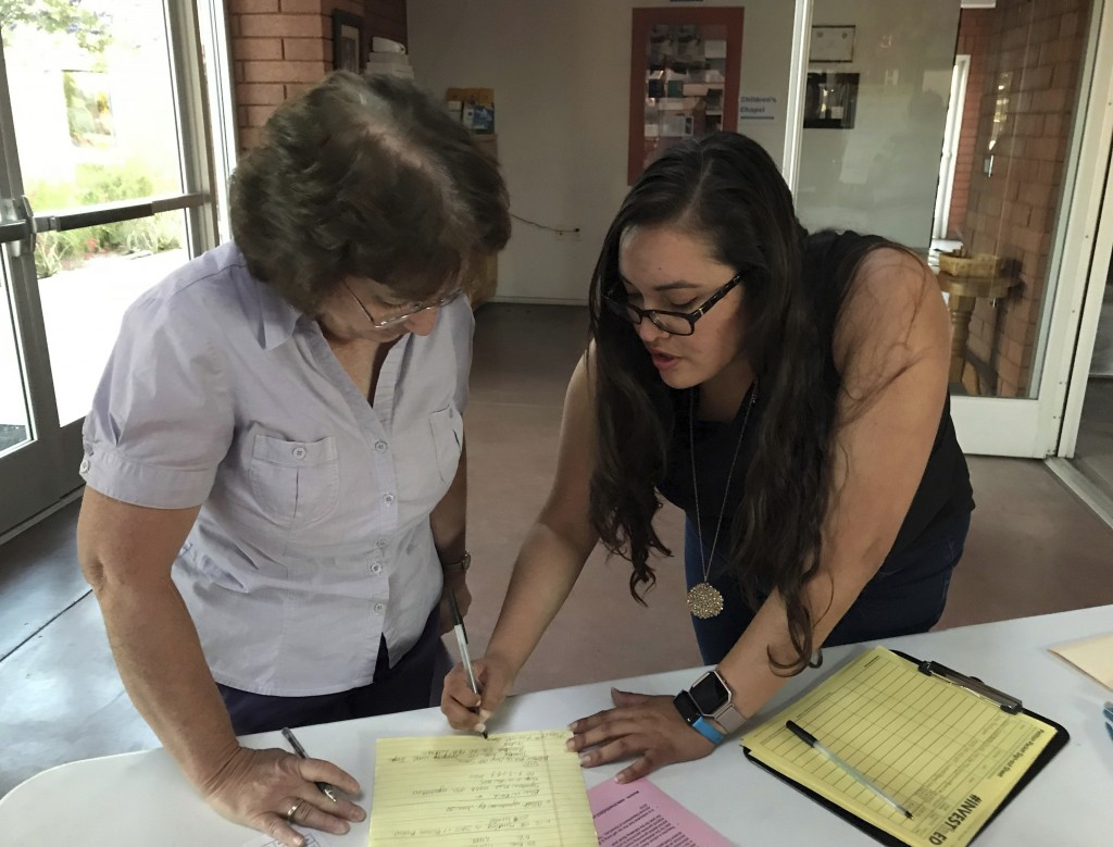 Liz Leivas, co-president of Tempe Education Association, right, gathers signatures Thursday, May 10, 2018 for ballot initiate to raise the income tax