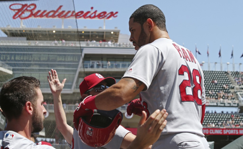 St. Louis Cardinals' Tommy Pham, right, is greeted in the dugout after he scored on a two-run single by Dexter Fowler off Minnesota Twins pitcher Lanc...