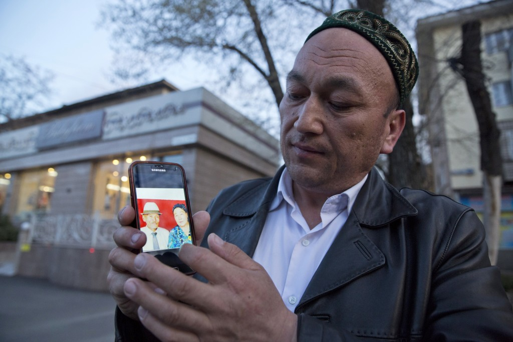 In this March 31, 2018, photo, Omir Bekali holds up a mobile phone showing a photo of his parents whom he believes have been detained in China, in Alm