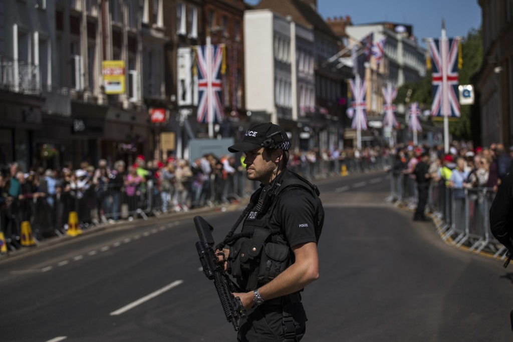 A police officer keeps guard at a street in Windsor, England, Thursday, May 17, 2018, during a rehearsal for the procession of the upcoming wedding of