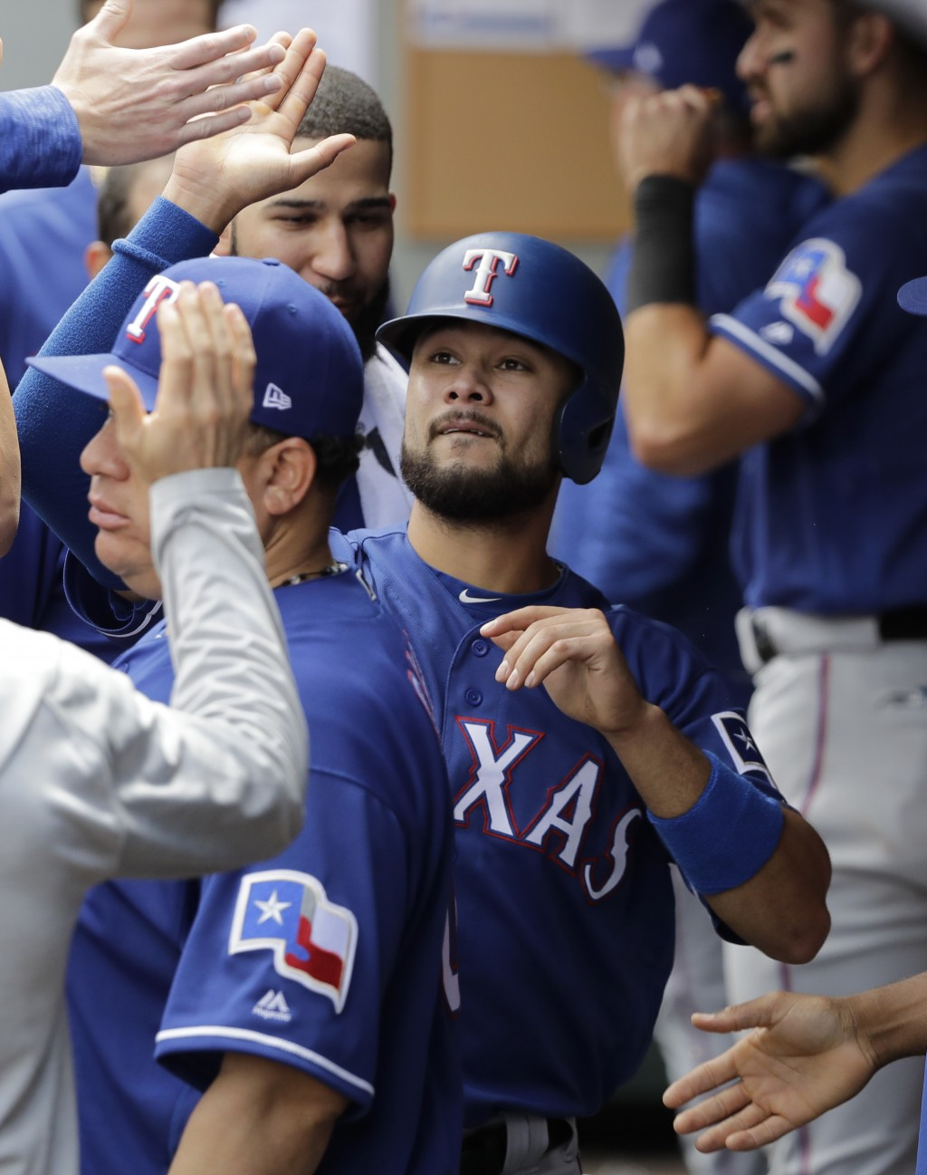 Texas Rangers' Isiah Kiner-Falefa, center, is greeted in the dugout after he scored on an RBI double hit by Delino DeShields during the eighth inning