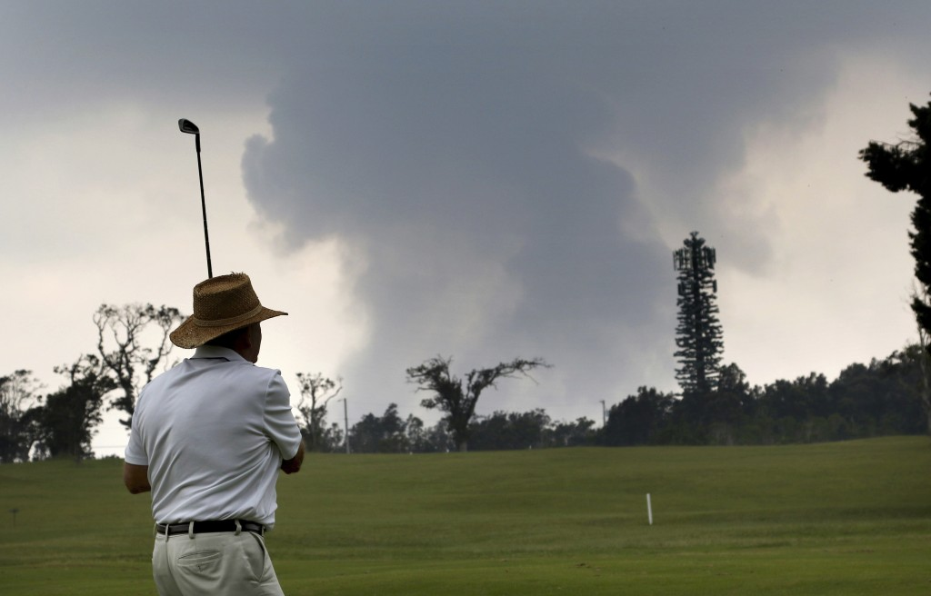 Ken McGilvray, of Keaau, Hawaii, golfs in Volcano, Hawaii as ash from the summit crater of Kilauea volcano rises in the background, Wednesday, May 16,