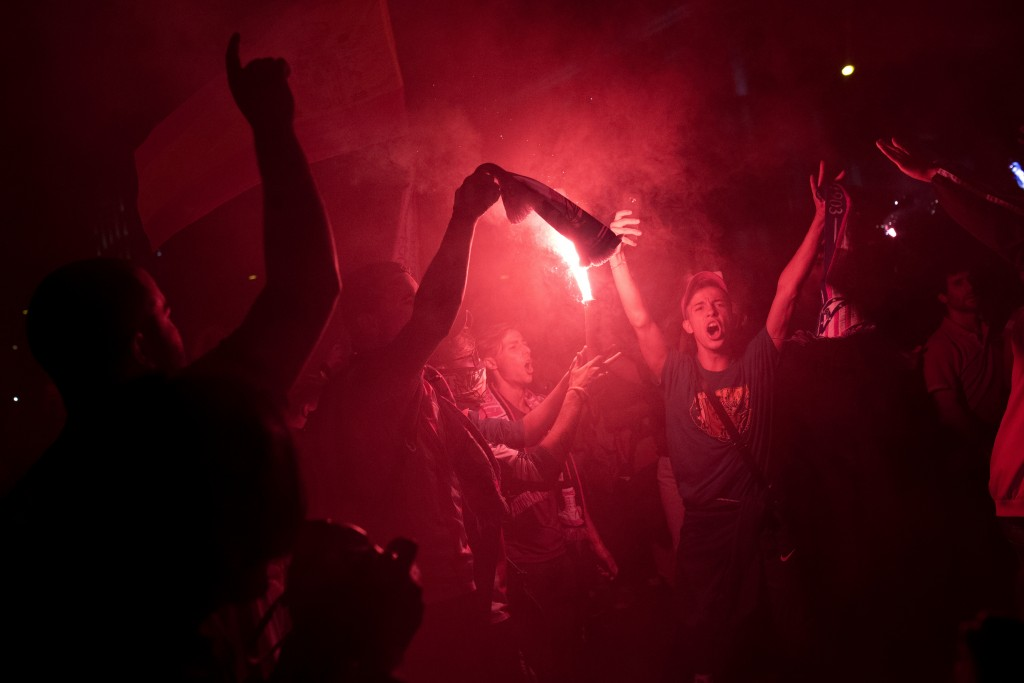 Atletico Madrid supporters light flares as they celebrate their team's Europa League title in Madrid, Wednesday, May 16, 2018. Atletico defeated Marse