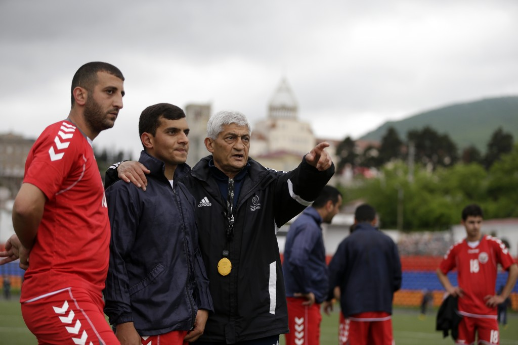 In this Friday, May 11, 2018 photo, Slavik Gabrielvan, right, the coach of the soccer national team of the self-proclaimed Republic of Artsakh gives d