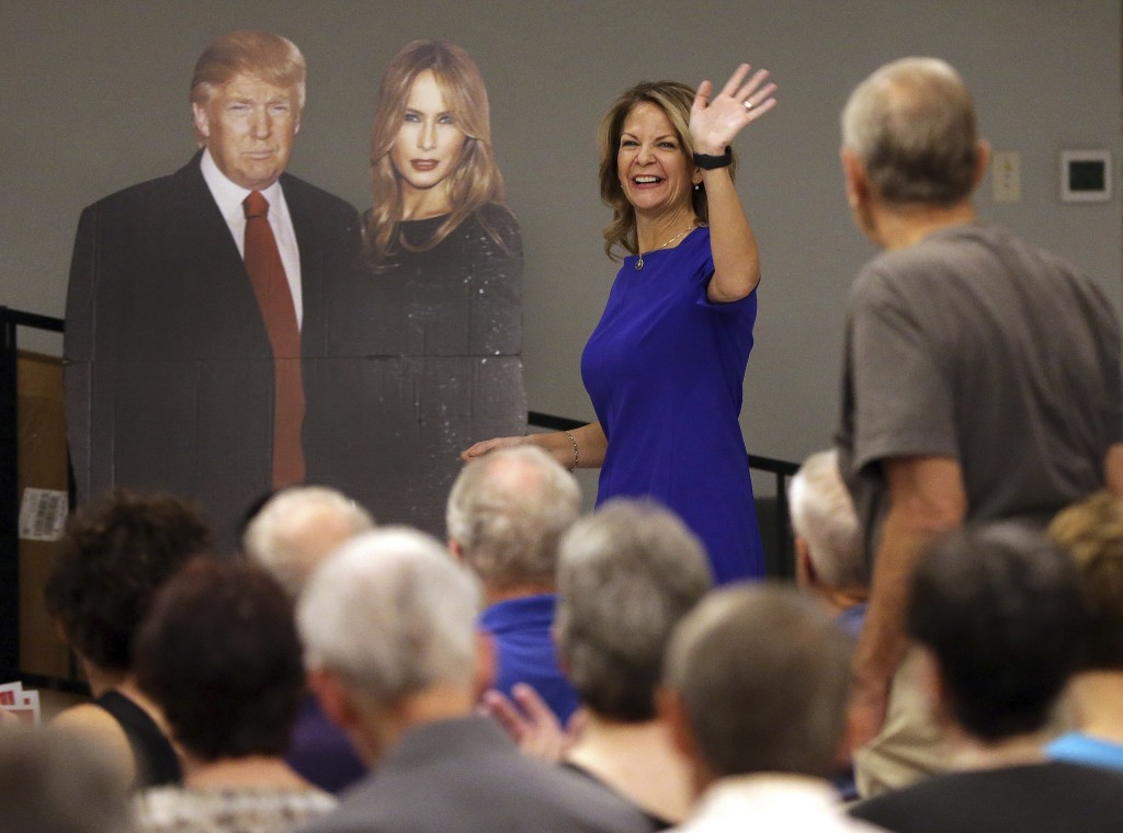 In this Tuesday, May 8, 2018 photo, U.S. Senatorial candidate Kelli Ward waves to volunteers and voters as she walks past a cardboard cut-out of Presi