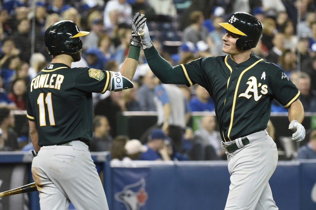 Oakland Athletics' Matt Chapman, right, celebrates his two-run home run with Dustin Fowler (11) during the sixth inning of a baseball game against the