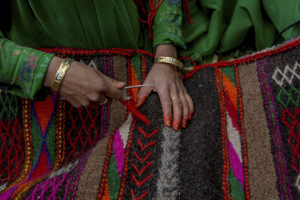 In this May 9, 2018, photo, a Kashmiri nomadic Bakarwal woman decorates a blanket made from goat hair outside her tent in Newa, 29 kilometers (18 mile