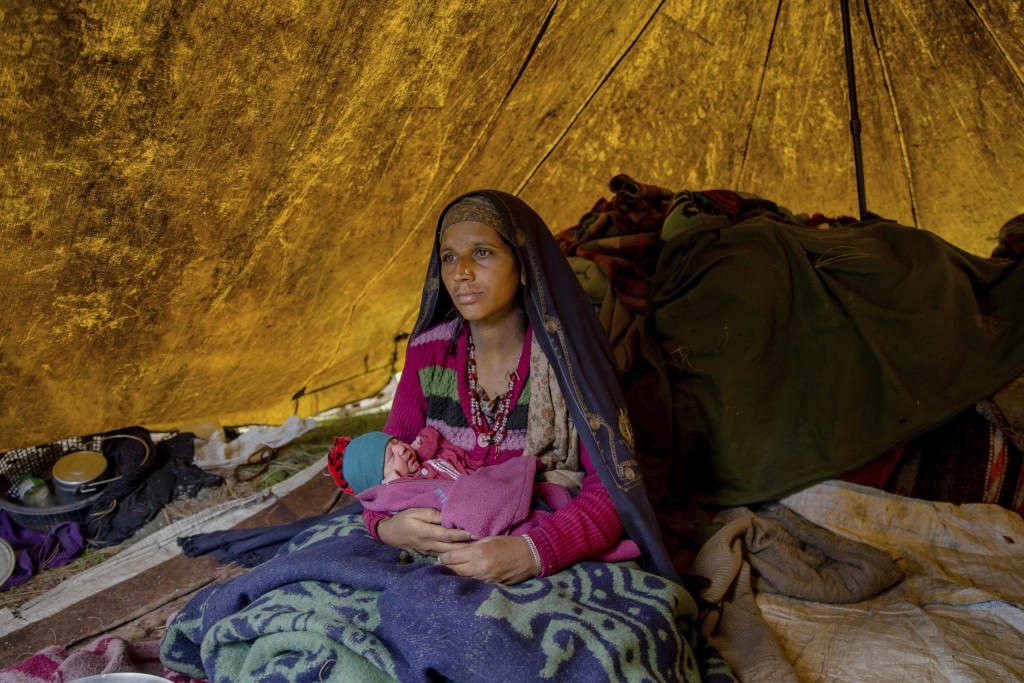 In this May 9, 2018, photo, Nasreen Bano, a Kashmiri nomadic Bakarwal woman poses for pictures along with her new born baby girl inside her tent at a