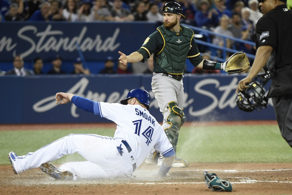 Toronto Blue Jays' Justin Smoak (14) slides into home plate to score a run as Oakland Athletics catcher Jonathan Lucroy (21) stands nearby during the