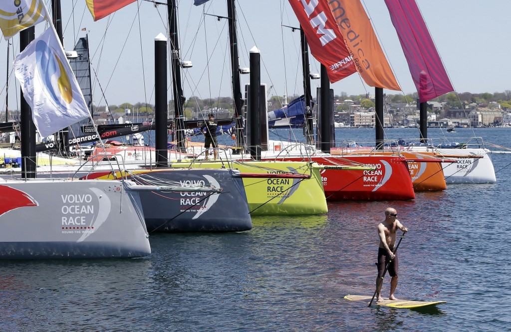 FILE - In this May 7, 2015, file photo, a man on a paddle board floats past racing yachts from the international Volvo Ocean Race, docked in Newport H