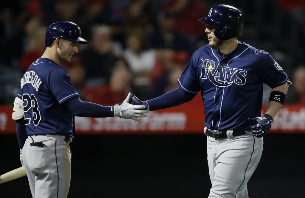 Tampa Bay Rays designated hitter C.J. Cron, right, gets congratulations from Daniel Robertson after hitting a solo home run against the Los Angeles An