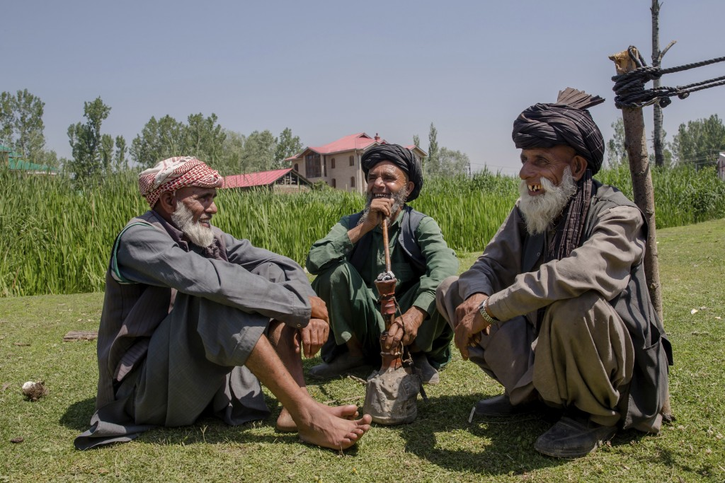 In this May 11, 2018, photo, photo, elderly Kashmiri nomadic Bakarwal men share a lighter moment as the smoke a hubble bubble or Hukka near a camp, ou