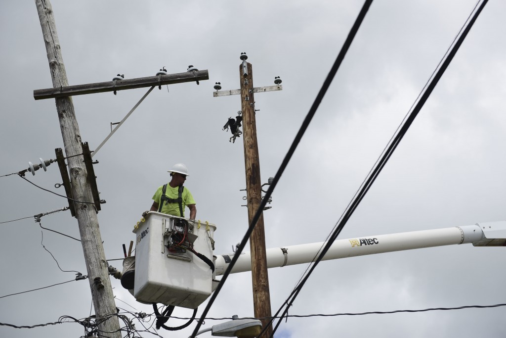 In this May 16, 2018 photo, a worker with Cobra Energy Company, contracted by the Army Corps of Engineers, installs power lines in the Barrio Martorel
