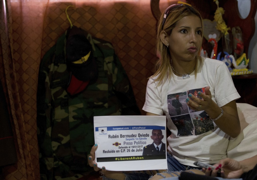 In this Feb. 22, 2018 photo, Odalys Bermudez holds a sign featuring her brother, a jailed National Guard Sergeant Ruben Bermudez, during a interview i