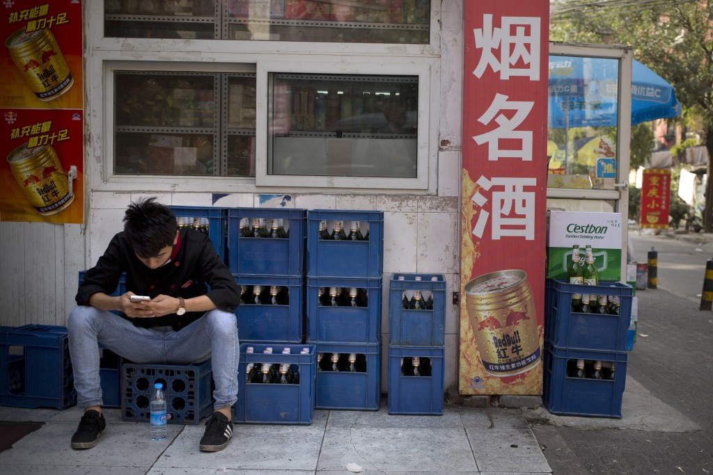 FILE - In this Thursday, Oct. 15, 2015, photo, a restaurant worker sits on crates of beer outside a convenience store as he uses his smartphone in Bei