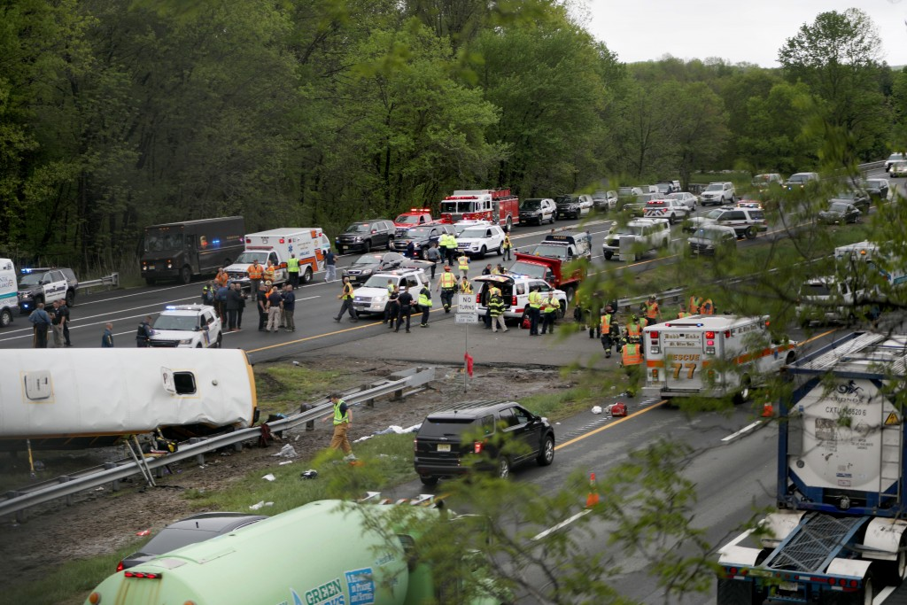Emergency personnel work at the scene of a school bus and dump truck collision, injuring multiple people, on Interstate 80 in Mount Olive, N.J., Thurs