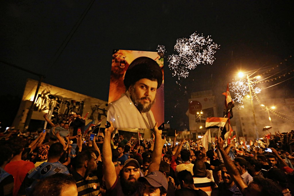 FILE - In this May 14, 2018, file photo, followers of Shiite cleric Muqtada al-Sadr, seen in the poster, celebrate in Tahrir Square, Baghdad, Iraq. Fo