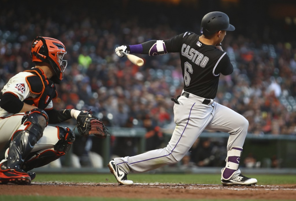 Colorado Rockies' Daniel Castro and San Francisco Giants catcher Buster Posey watch Castro's two-run double hit off Giants pitcher Jeff Samardzija dur