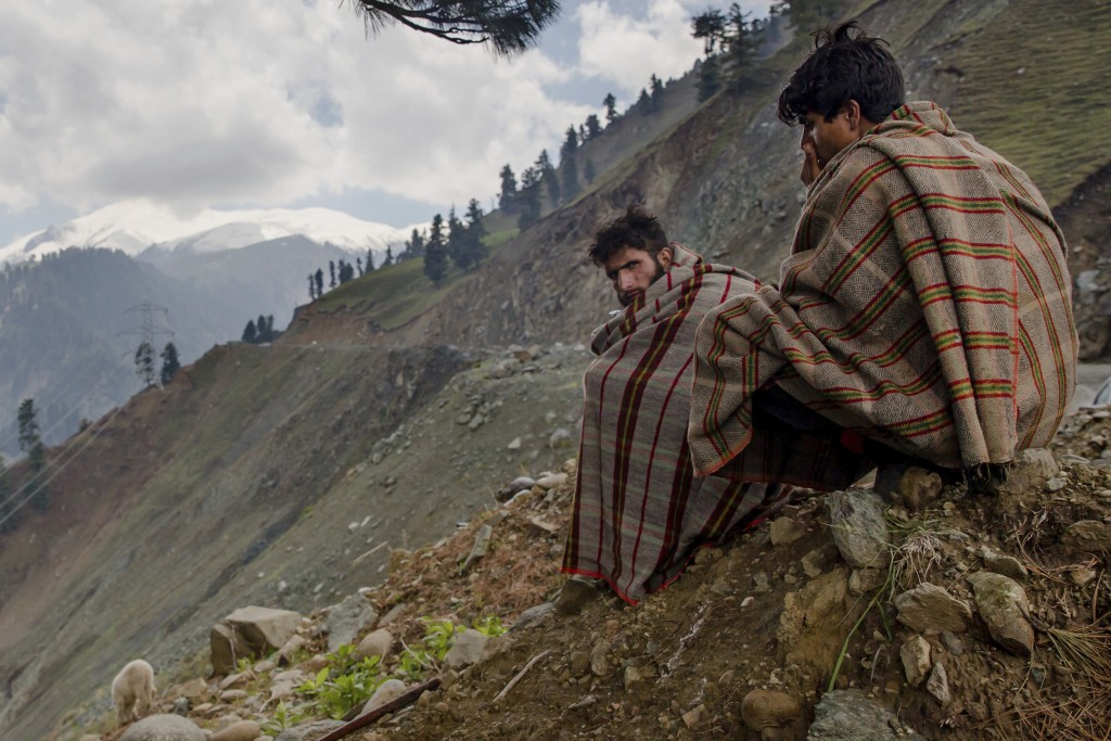 In this May 9, 2018, photo, Kashmiri nomadic Bakarwal men keep an eye on the heard of sheep and goats as they take shelter under a tree as it drizzles