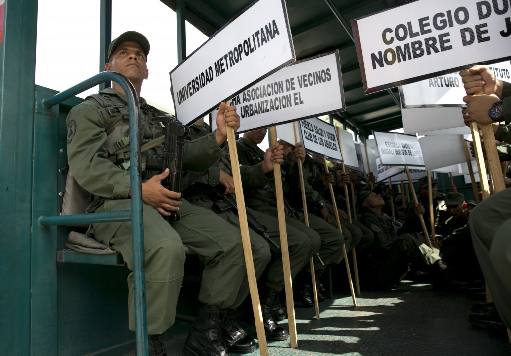 FILE - In this May 15, 2018 file photo, soldiers hold signs of the names of schools that will serve as voting centers as they leave the Military Acade