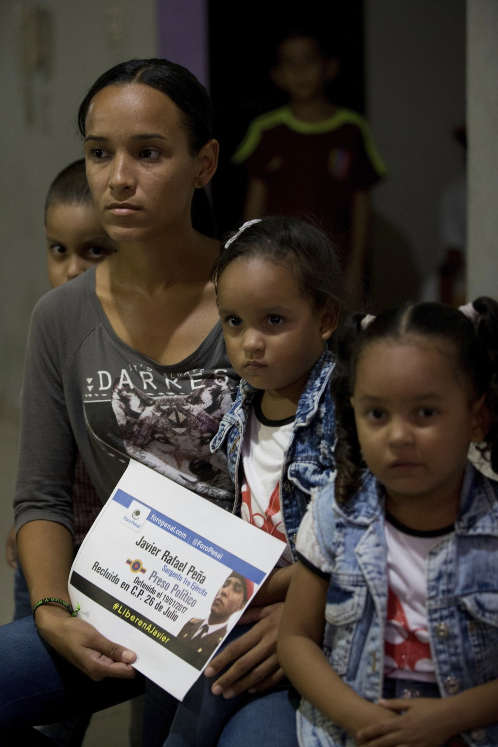 In this Feb. 22, 2018 photo, Ariana Lovera holds a photo of her husband, jailed Army Sergeant Javier Rafael Pena, alongside her daughters Helen, cente