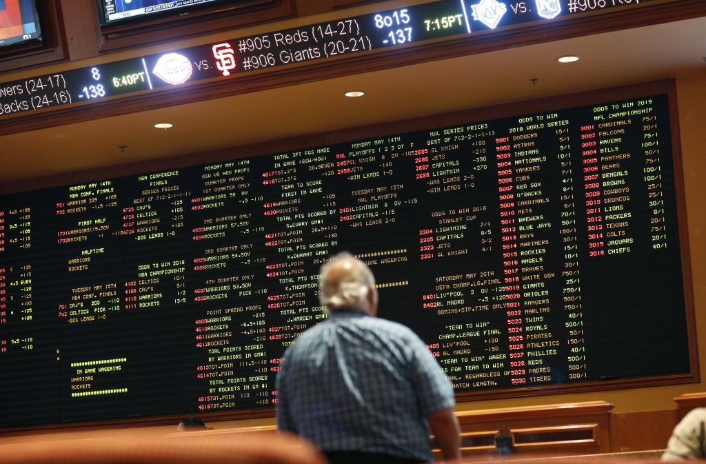 FILE - In this Monday, May 14, 2018 file photo, betting odds are displayed on a board in the sports book at the South Point hotel and casino in Las Ve