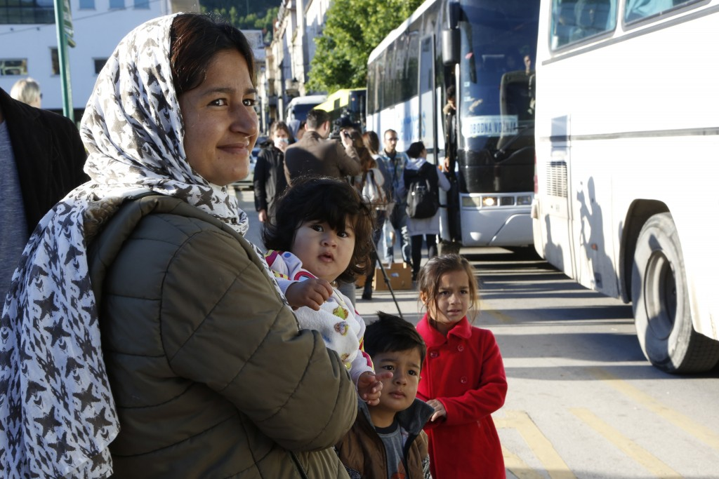 A woman holds a child in her arms as as they board buses, during the evacuation of a makeshift camp in a park across the City Hall, in Sarajevo, on ea