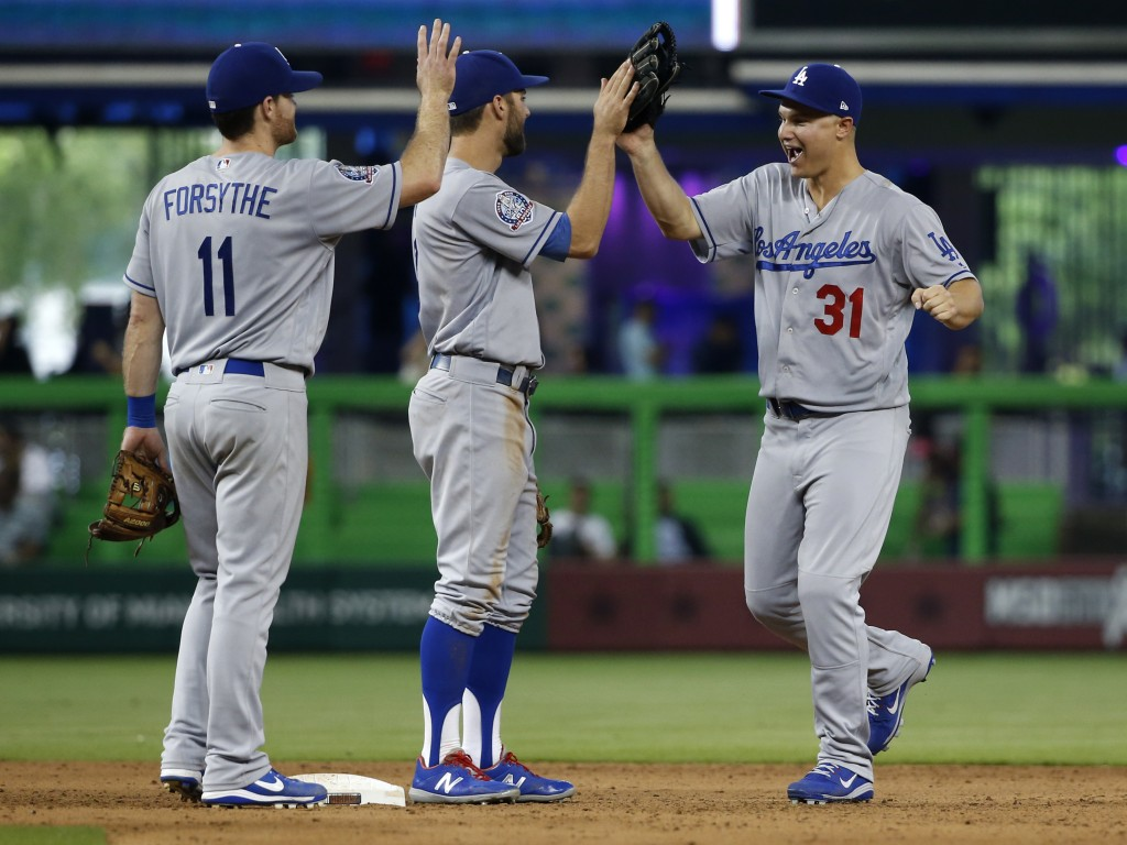 Los Angeles Dodgers players Logan Forsythe (11), Chris Taylor, center, and Joc Pederson (31) celebrate after the Dodgers defeated the Miami Marlins 7-
