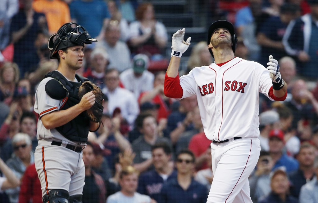 Boston Red Sox's J.D. Martinez, right, celebrates his two-run home run in front of Baltimore Orioles' Andrew Susac during the first inning of a baseba