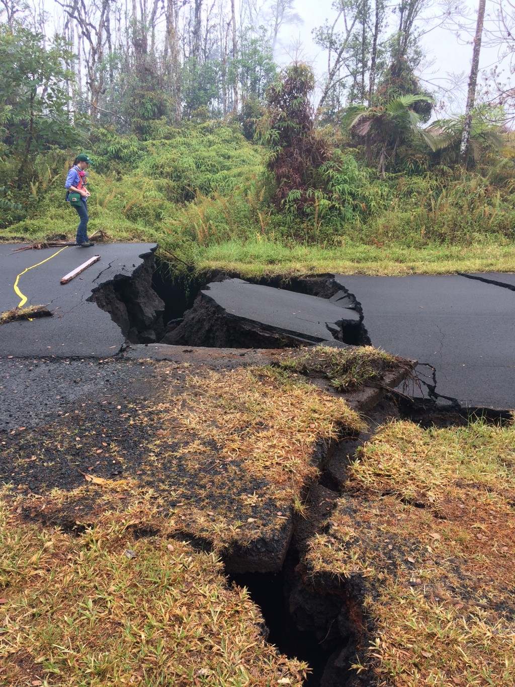 In this Thursday, May 17, 2018 image released by the U.S. Geological Survey, a Hawaiian Volcano Observatory, HVO geologist monitors the the vertical o