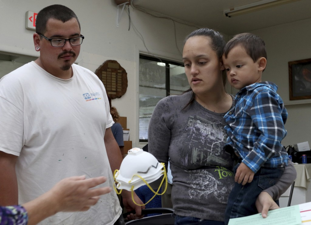 Lindsey Magnani, center, her finance Elroy Rodrigues, left, and their children, Kahele, right, and Kayden, not shown, pick up respirators to help prot