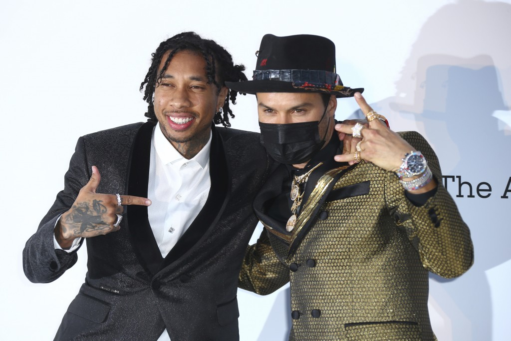 Rapper Tyga, left, and artist Alec Monopoly pose for photographers upon arrival at the amfAR, Cinema Against AIDS, benefit at the Hotel du Cap-Eden-Ro