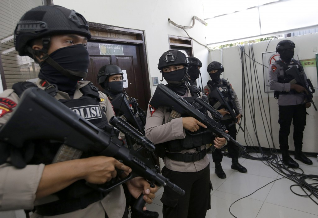 Armed officers stand guard during the trial of Islamic cleric Aman Abdurrahman who is accused of being the key ideologue for IS militants in Indonesia