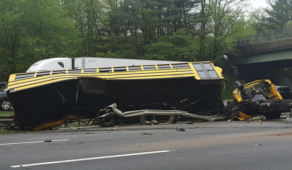 This photo shows an overturned school bus after it collided with a dump truck, injuring multiple people, on Interstate 80 in Mount Olive, N.J., Thursd