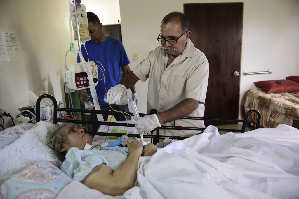 In this May 16, 2018 photo, Alberto Rodriguez gives water to his wife Mirella Sepulveda who suffered a stroke in Yabucoa, a town where many continue w