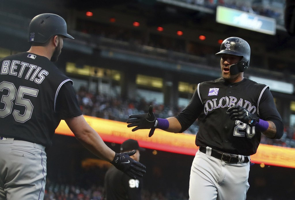 Colorado Rockies' Ian Desmond, right, celebrates with Chad Bettis (35) after scoring against the San Francisco Giants during the second inning of a ba