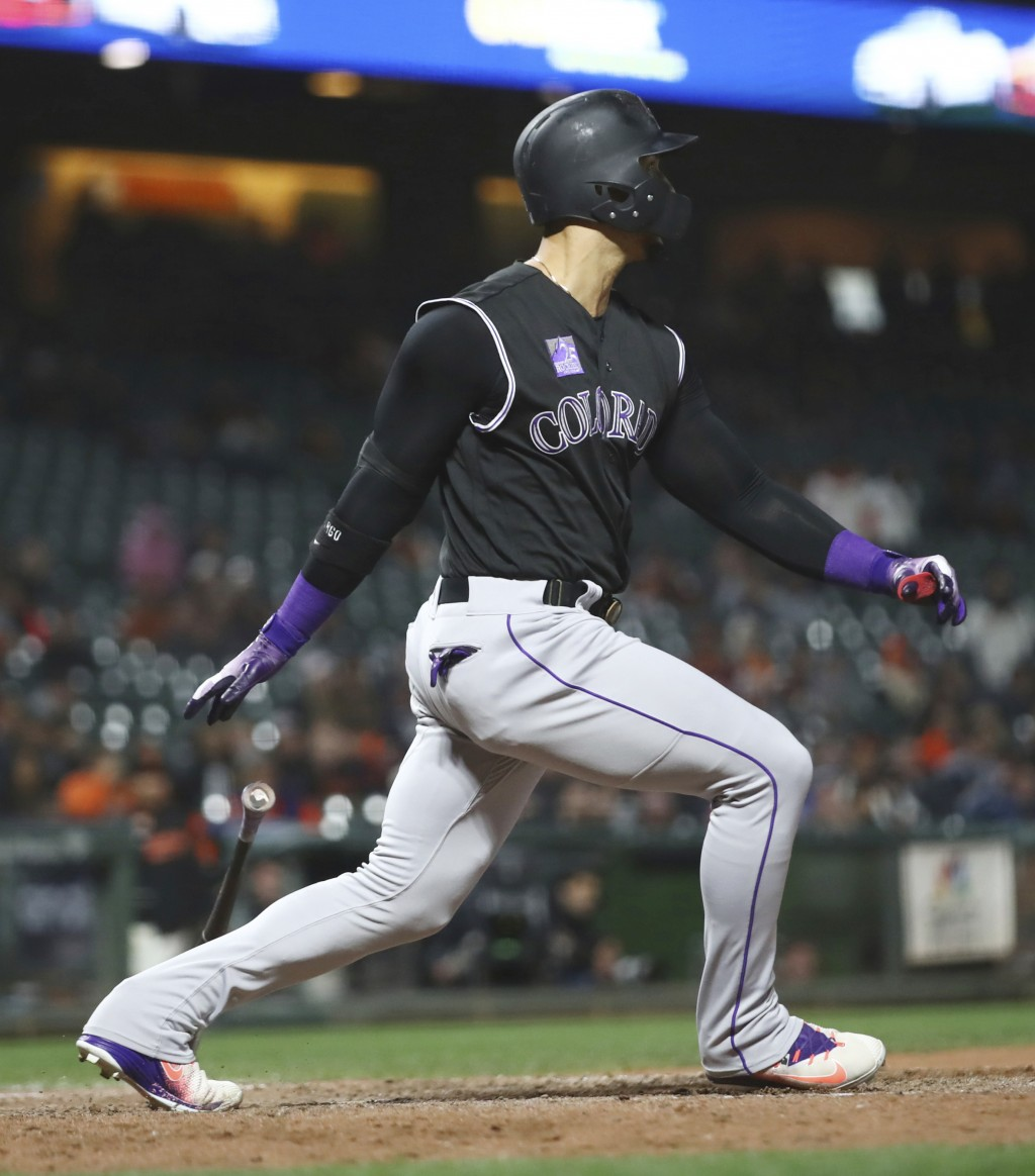 Colorado Rockies' Carlos Gonzalez swings for a two run single against the San Francisco Giants in the 12th inning of a baseball game Thursday, May 17,