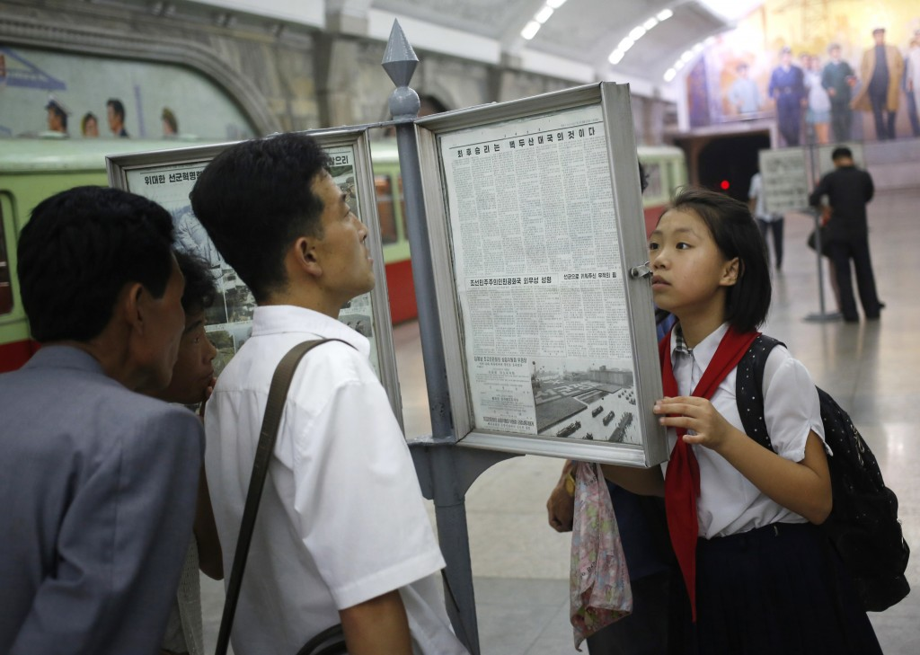FILE - In this Aug. 22, 2015, file photo, people read the newspaper at a subway train platform in Pyongyang, North Korea. Donald Trump and Kim Jong Un