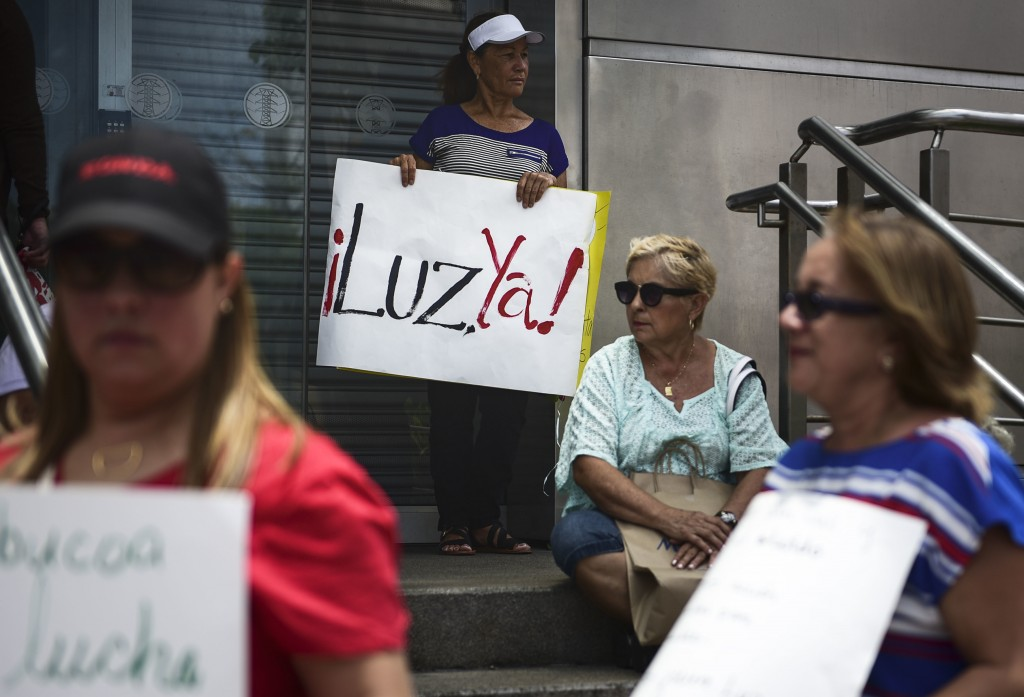 In this May 15, 2018 photo, residents from Yabucoa, where many are still without power, protest outside the Electric Power Authority office, demanding