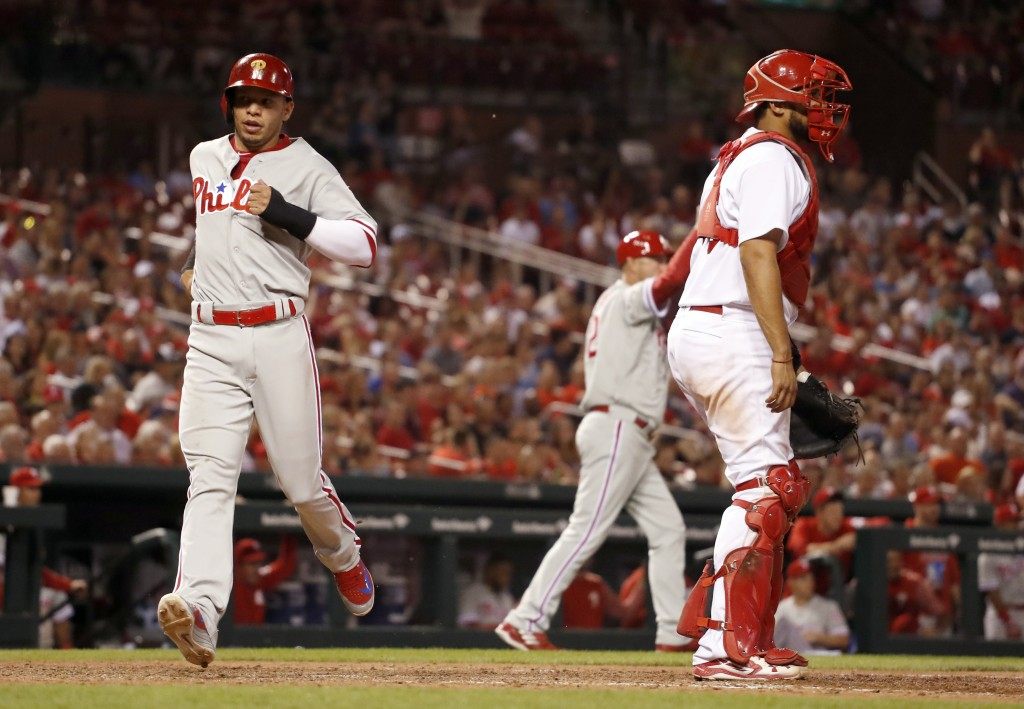 Philadelphia Phillies' Cesar Hernandez, left, scores past St. Louis Cardinals catcher Francisco Pena on a double by Odubel Herrera during the eighth i