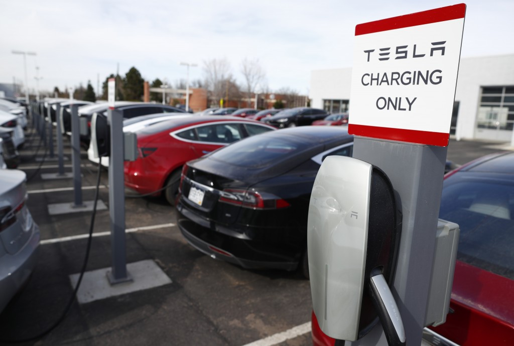FILE - In this April 15, 2018, photo, unsold 2018 models sits amid a series of charging stations on a Tesla dealer's lot in the south Denver suburb of