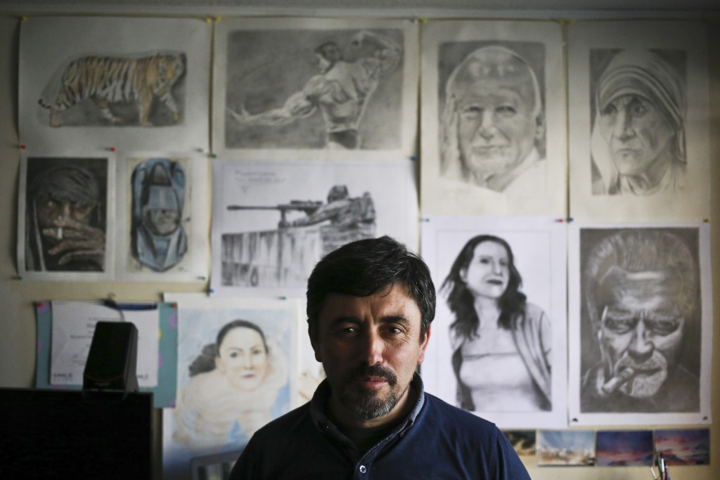 In this May 8, 2018 photo, cartoonist Eladio Valdes poses for a photo inside his home studio, in Santiago, Chile. Valdes says the same religious broth