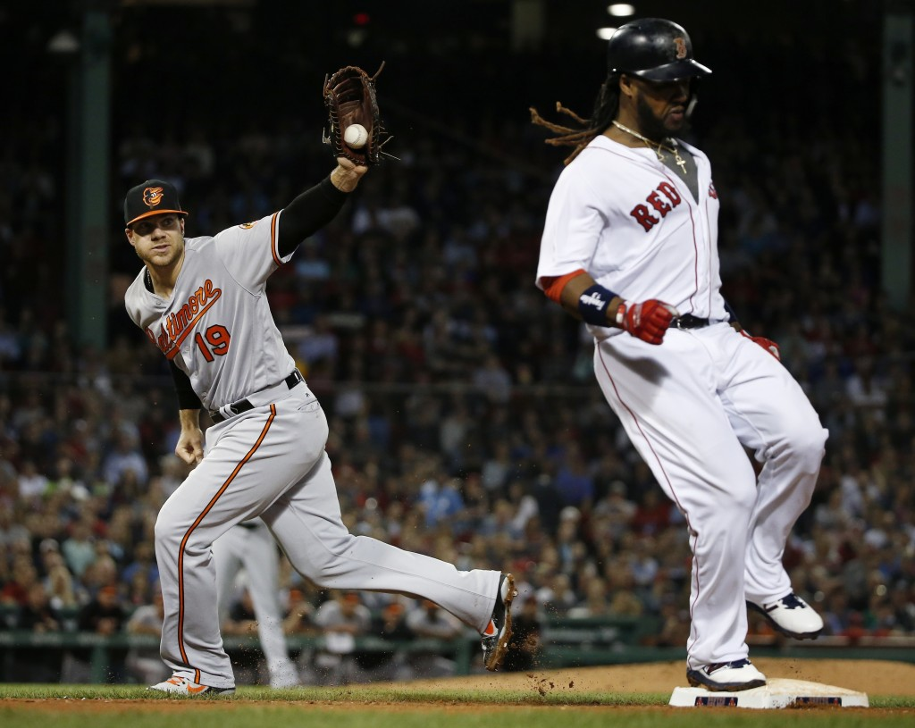 Boston Red Sox's Hanley Ramirez, right, reaches first with a single after Baltimore Orioles' Chris Davis (19) was pulled off base by the throw during