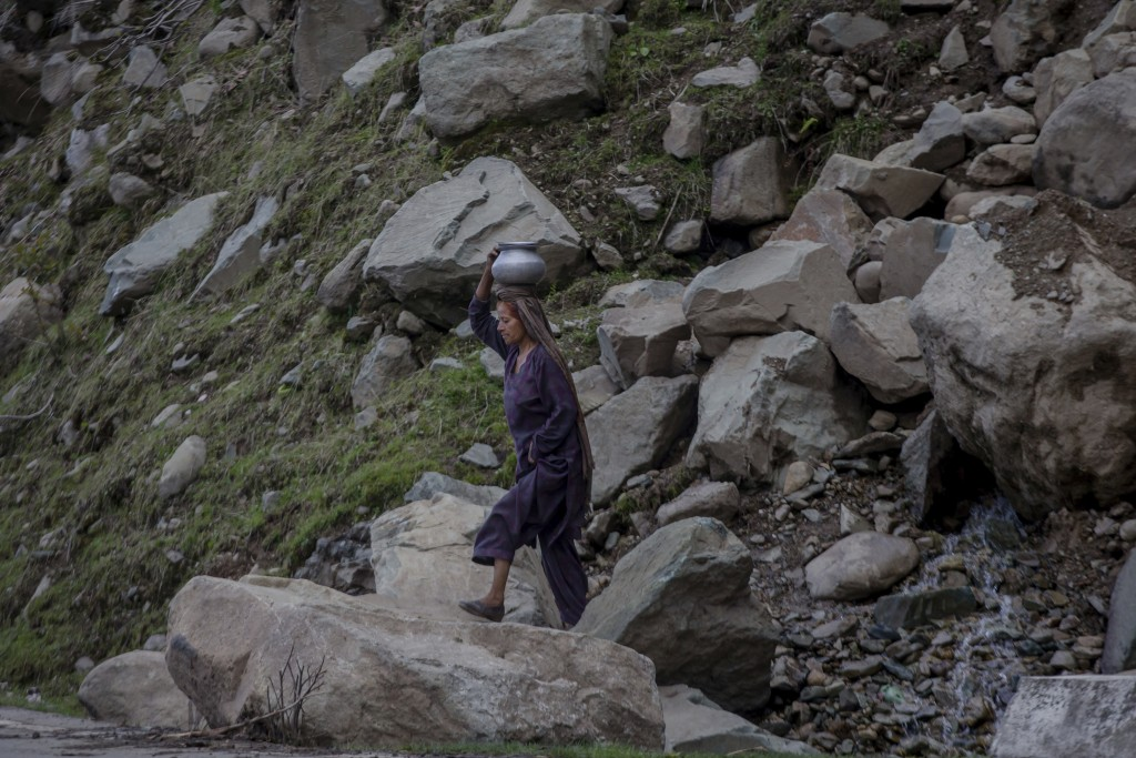 In this May 9, 2018, photo, a Kashmiri nomadic Bakarwal woman carries water after collecting it from a waterfall in Dubgan, 70 kilometers (43 miles) s