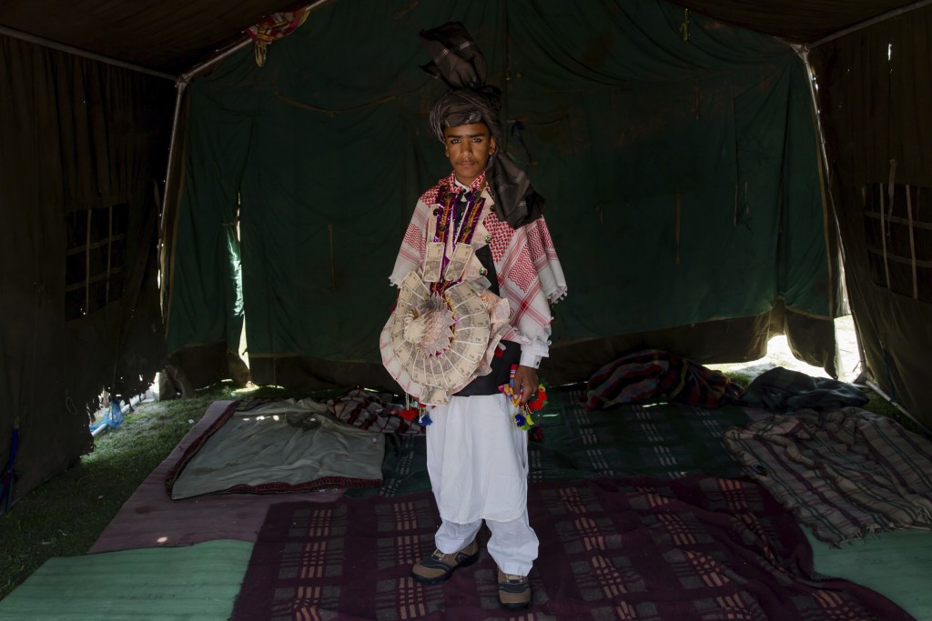 In this May 11, 2018, photo, Mushtaq Khan, a Kashmiri nomadic Bakarwal groom poses for picture inside a tent at a camps in outskirts of Srinagar, Indi