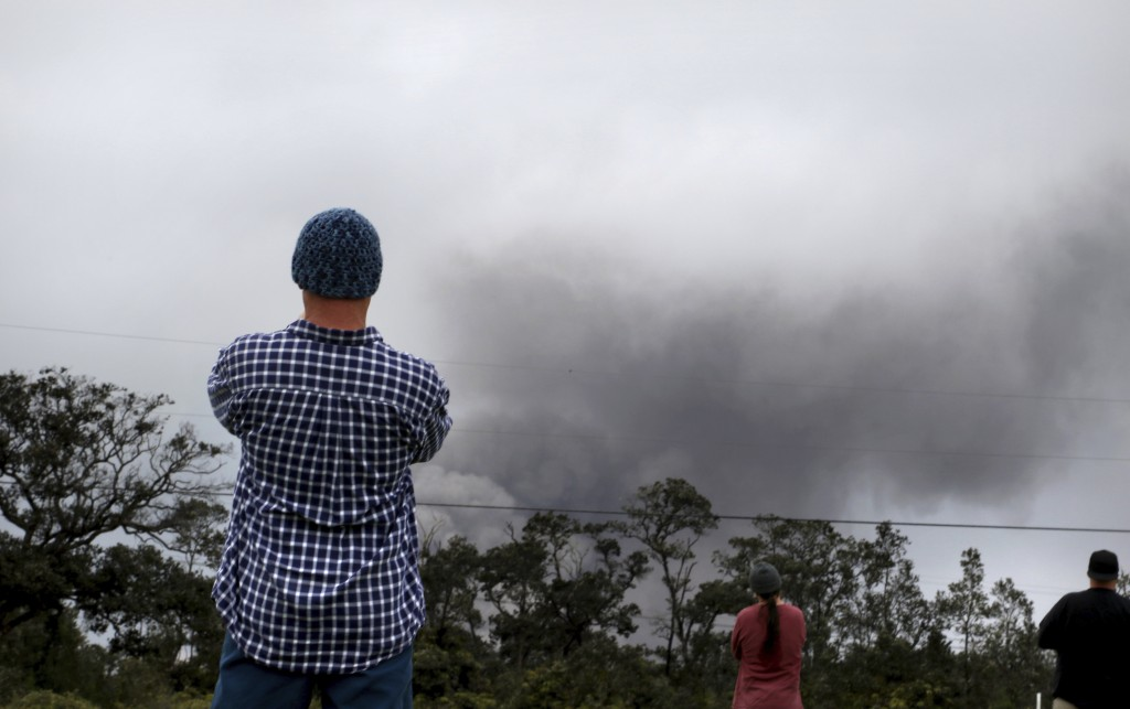 Joe Laceby, 47, of Volcano, Hawaii, watches as ash rises from the summit crater of Kilauea volcano, Thursday, May 17, 2018, in Volcano, Hawaii. Laceby
