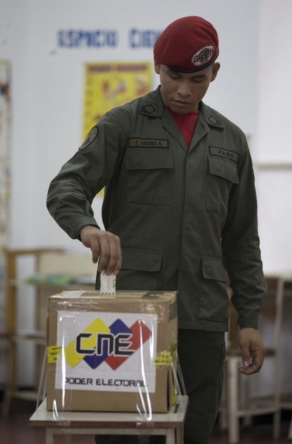 FILE - In this Dec.10, 2017 file photo, a soldier votes during mayoral elections in Caracas, Venezuela. In 2018, the 150,000 men and women serving in