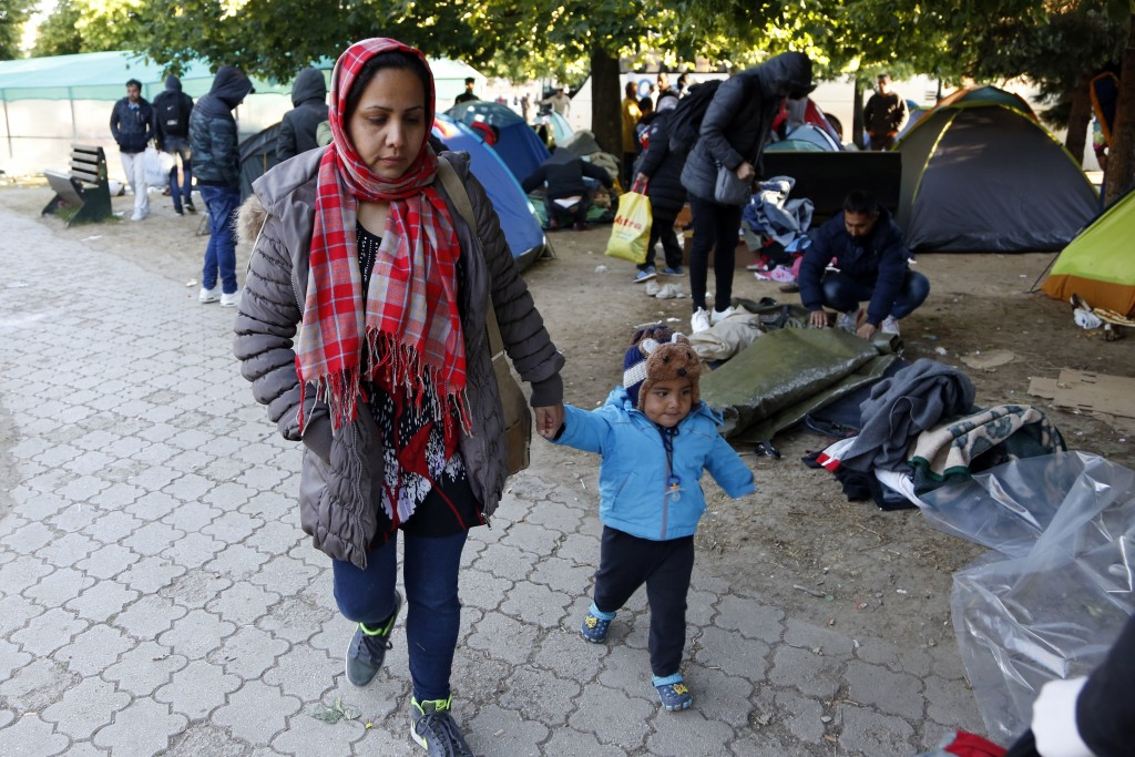 A woman holds a child as migrants pack their belongings and their tents during the evacuation of a makeshift camp in a park across the City Hall, in S