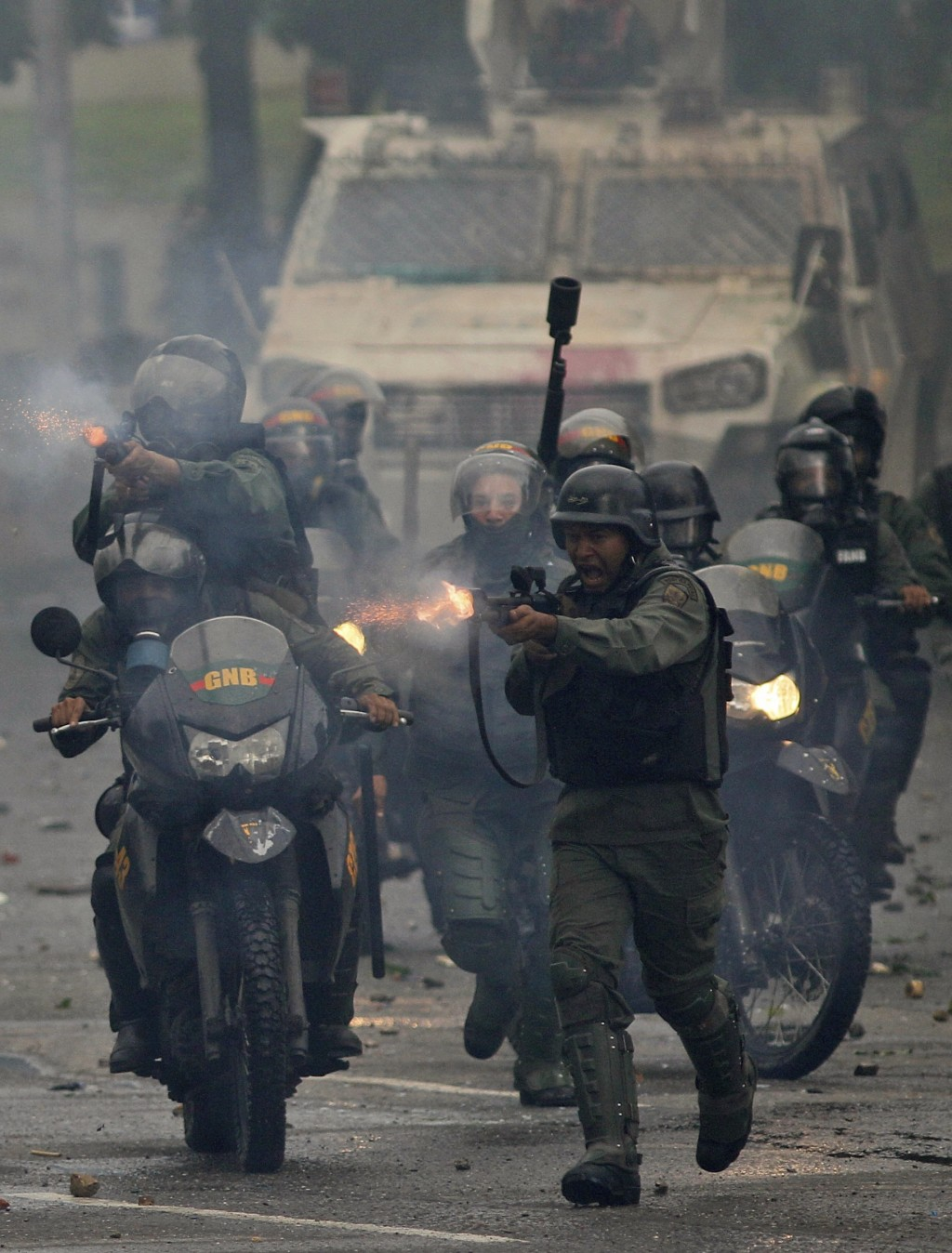 FILE - In this July 28, 2017 file photo, Bolivarian National Guards advance on anti-government demonstrators with rubber bullets in Caracas, Venezuela